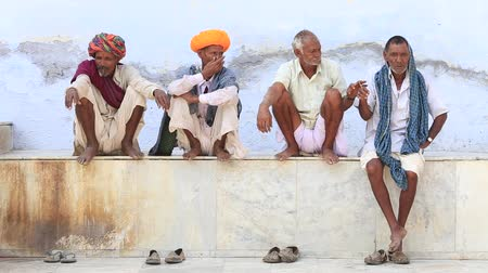 négy ember : PUSHKAR, INDIA - OCTOBER 25, 2014: Unidentified Indian four men, sits on the ghat along the sacred Sarovar lake. Pushkar - famous worship place in India
