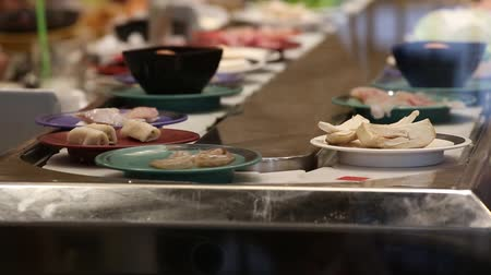 Японская культура : Various japanese food in a conveyor belt at restaurant in Pattaya, Thailand Стоковые видеозаписи