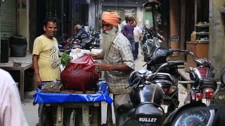 asian and indian ethnicities : AMRITSAR INDIA SEPTEMBER 28 2014: Unidentified Indian man in a narrow street sells local drink Stock Footage