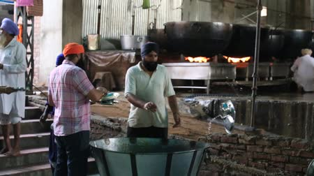 hacı : AMRITSAR INDIA SEPTEMBER 27 2014: Unidentified poor indian people clean dishes at a soup kitchen in the Sikh Golden Temple Stok Video