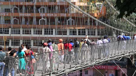 hobo : RISHIKESH INDIA 09 OCTOBER 2014: Unidentified people crossing Laxman Jhula footbridge on river Ganga by the Tera Manzil Temple. Indian people flock to Rishikesh for charity.