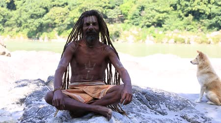 hobo : RISHIKESH INDIA OCTOBER 2014: Unidentified poor man sits on the ghat along the Ganges river. Poor Indians flock to Rishikesh for charity. Stock Footage