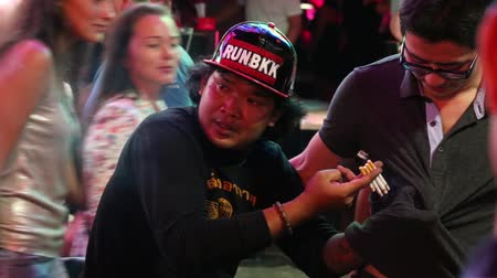 gimmick : PATTAYA THAILAND NOVEMBER 15 2014: Thai man showing tricks with a cigarette on a Walking Street. Walking Street is redlight district with many restaurants gogo bars and brothels