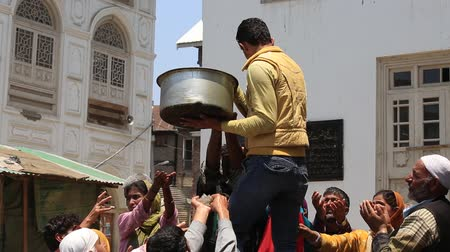 éhség : SRINAGAR, INDIA - JUNE 11, 2015: Unknown Indian man feeds the hungry people near a Muslim mosque. Kashmiris are fighting for their freedom for 20 years now. Kashmir became dangerous again.