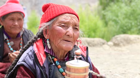 törzsi : LAMAYURU, INDIA - JUNE 13, 2015: Unidentified buddhist old women during Tsam mystery in time of Yuru Kabgyat festival at Lamayuru Gompa, Ladakh, North India Stock mozgókép