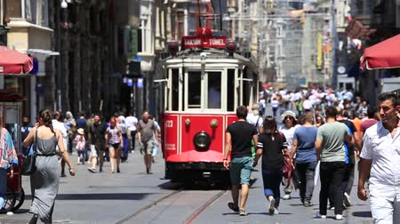 uliczki : ISTANBUL, TURKEY - JULY 21, 2014: The Taksim Tunel Nostalgia Tram trundles along the istiklal street and crowded people at istiklal avenue Wideo