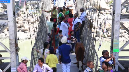 hobo : RISHIKESH, INDIA - OCTOBER 11, 2014: Unidentified people crossing Laxman Jhula footbridge on river Ganga by the Tera Manzil Temple. Indian people flock to Rishikesh for charity.