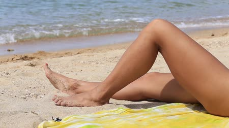 nogi : Beautiful tanned womens legs at the beach. Close up
