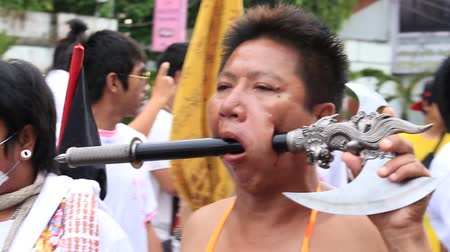 possessed : PHUKET, THAILAND - OCT 18, 2015: Chinese thai monk possessed by his god walks with his mouth pierced in Vegetarian Festival at Phuket Town. Festival is a famous annual also known as Nine Emperor Gods