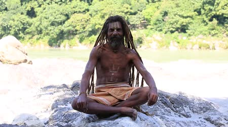 evsiz : RISHIKESH, INDIA - OCTOBER 11, 2014: Unidentified poor man sits on the ghat along the Ganges river. Poor Indians flock to Rishikesh for charity. Stok Video