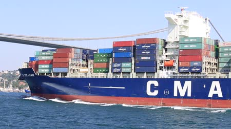 navios : ISTANBUL, TURKEY - JULY 29, 2015: CMA CGM stacked containers on the deck of cargo ship sailing in Bosporus Sea