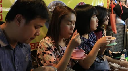 konserve : BANGKOK, THAILAND - JANUARY 06, 2016: People eating street food in Chinatown. Yaowarat Road China Town is famous for its night life for dining and eating with lively environment.