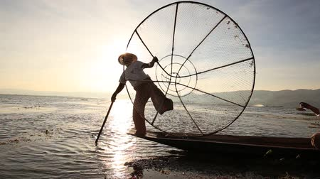 fishermen : INLE LAKE, MYANMAR - JANUARY 14, 2016: Unidentified Burmese fisherman on bamboo boat catching fish in traditional way with handmade net