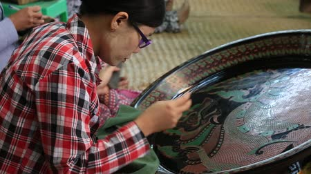 caseiro : BAGAN. MYANMAR - JANUARY 22, 2016: Unidentified Burmese woman working in a factory of lacquer. Lacquerware includes boxes, tableware, buttons and souvenirs