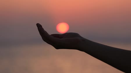 nadzieja : Hand catching a sun against beautiful sunset on horizon. Nature. Vacation. Hope. Freedom concept. Womans hand. Island Koh Samui, Thailand