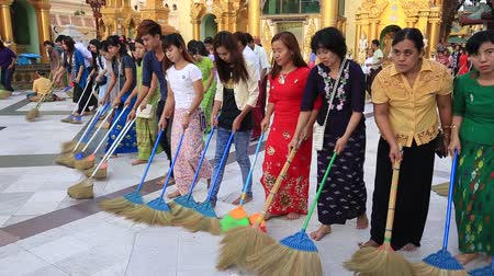 besom : YANGON, MYANMAR - JANUARY 9, 2016: Unidentified group of pilgrims participate in a ceremony with brooms at the Shwedagon Pagoda. Shwedagon Pagoda is the most sacred Buddhist pagoda for the Burmese