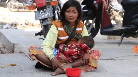 local population : MANDALAY, MYANMAR - JANUARY 16, 2016: Unidentified poor woman with a child begging money from people on the street. Poverty is a major issue in Burma Stock Footage