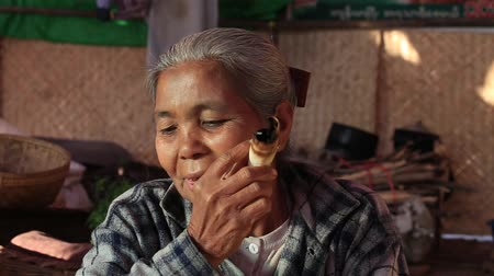 mianmar : BAGAN, MYANMAR - JANUARY 20, 2016: Unidentified Burmese old woman smoking a big handmade cigar. Footage taken in a little village, where a woman does cigars by herself and smoke them proudly Stock mozgókép
