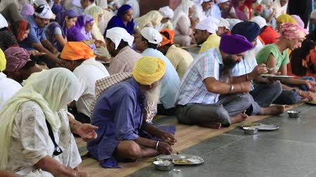 hacı : AMRITSAR, INDIA - SEPTEMBER 26, 2014: Unidentified poor indian people eating free food at a soup kitchen in the Golden Temple