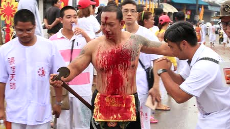 bloodshed : PHUKET, THAILAND - OCT 18, 2015: Chinese thai monk possessed by his god walks with his mouth pierced in Vegetarian Festival at Phuket Town. Festival is a famous annual also known as Nine Emperor Gods