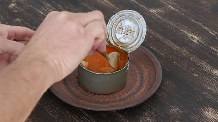 molho de tomate : Man eating canned fish in tomato sauce with bread