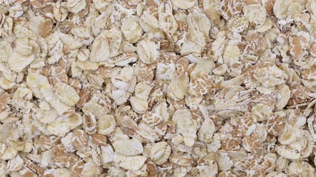 yulaf ezmesi : Rolled oats grains close up. Loop rotation. Front of the camera rotates plate with oats