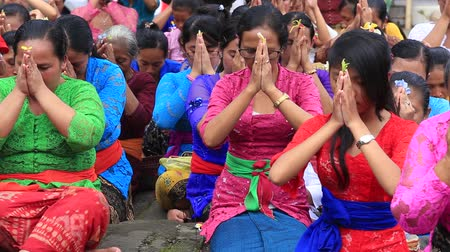 templom : UBUD, BALI, INDONESIA - MARCH 20, 2015: Unidentified Indonesian people celebrate Balinese New Year and the arrival of spring. Women praying at holy temple during the religious ceremony