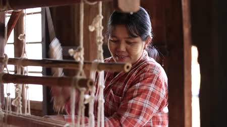 machine sous : INLE LAKE, MYANMAR - JANUARY 12, 2016: Traditional Burmese textile manufacture in craft village where women work on wooden weaving loom machines and spin yarn creating silk or cotton fabric