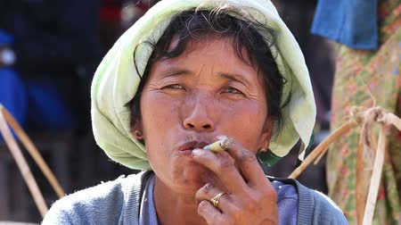Бирма : INLE LAKE, MYANMAR - JANUARY 12, 2016: Unidentified Burmese old woman smoking a big handmade cigar. Footage taken in a little village, where a woman does cigars by herself and smoke them proudly Стоковые видеозаписи