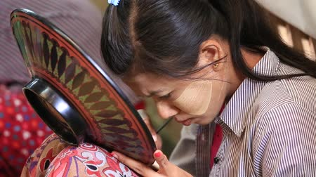 lacquerware : BAGAN. MYANMAR - JANUARY 22, 2016: Unidentified Burmese woman working in a factory of lacquer. Lacquerware includes boxes, tableware, buttons and souvenir