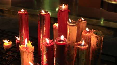 incenso : Red wax candles and incense sticks burning in a Buddhist temple. Bangkok, Thailand
