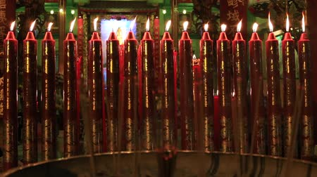 церковь : Red wax candles and incense sticks burning in a Buddhist temple. Bangkok, Thailand