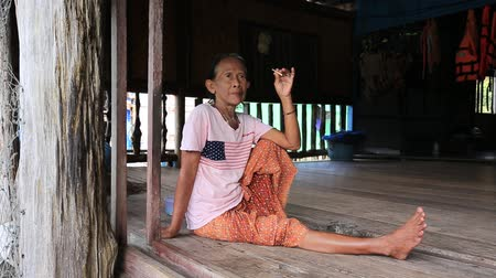 mianmar : KOH KOOD, THAILAND - JANUARY 29, 2015: Unknown old Thai woman smoking a cigarette on the terrace at home in the fishing village Stock mozgókép