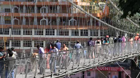 hobo : RISHIKESH, INDIA - OCTOBER 9, 2014: Unidentified people crossing Laxman Jhula footbridge on river Ganga by the Tera Manzil Temple. Indian people flock to Rishikesh for charity. Stock Footage