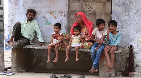 fome : PUSHKAR, INDIA - OCTOBER 25, 2014: An unidentified Indian family sits on the street begs for money from a passerby in Pushkar. Poverty is a major issue in India
