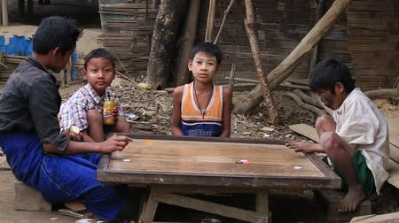 juventude : MRAUK-U, MYANMAR - JANUARY 28, 2016: Unidentified poor children playing a board game in the street