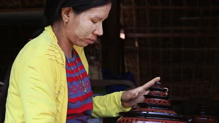 lacquerware : BAGAN, MYANMAR - JANUARY 19, 2016: Unidentified Burmese woman working in a factory of lacquer. Lacquerware includes boxes, tableware, buttons and souvenirs