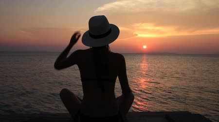 ciprus : Beautiful girl in a straw hat sitting on the beach during sunset. Koh Samui, Thailand