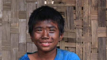 mianmar : MRAUK-U, MYANMAR - JANUARY 28, 2016: Unidentified portrait of a grimy boy working in the street garage. Due to poverty, children start working at an early age Stock mozgókép