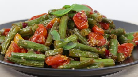 kavurma : Cooked green beans, red cherry tomato with sesame seeds in black plate, close up