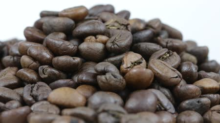 drink industry : Close up of coffee beans. Loop rotation. Front of the camera rotates plate with coffee beans