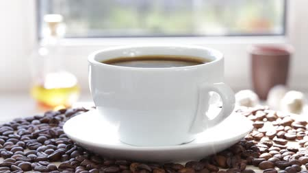 xícara de café : Rotation white cup with a black coffee and coffee beans. Black, steaming coffee in white cup. Close up.