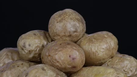 ve slupce : Ukrainian national dish is baked potatoes. Potato on a black background rotates, close up