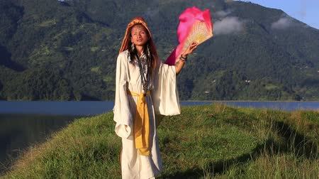mamífero : Shemale Sirena Sabiha dancing with a fan at sunrise in Pokhara, Nepal. Sirena was born in the Philippines. Close up