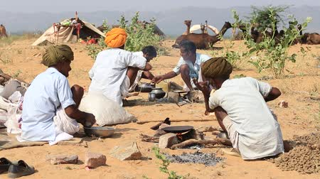 vila : PUSHKAR, INDIA - OCTOBER 28 2014: Unidentified Indian men cook food over a campfire during the Pushkar Camel Mela. This fair is the largest camel trading fair in the world