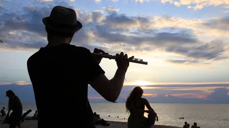 flutist : KOH PHANGAN, THAILAND - JANUARY 14, 2017: An unidentified man play the flute at sunset on the beach during a full moon party in island Koh Phangan, Thailand