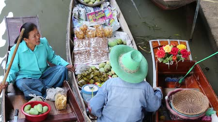 плавающий : RATCHABURI, THAILAND - APRIL 27, 2014: Unidentified people on food boats at Damnoen Saduak floating market. Damnoen Saduak is a very popular tourist attraction in Thailand.
