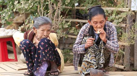 Бирма : BAGAN, MYANMAR - JANUARY 21, 2016: Unidentified Burmese old woman smoking a big handmade cigar. Footage taken in a little village, where a woman does cigars by herself and smoke them proudly