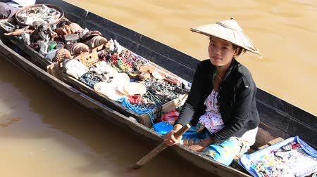 ıvır zıvır : INLE LAKE, MYANMAR - JANUARY 14, 2016: Unidentified Burmese woman on small long wooden boat selling souvenirs, trinkets and bijouterieat the floating market on Inle Lake, Myanmar