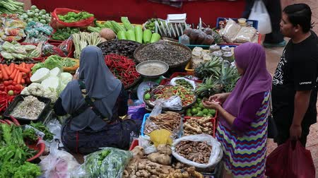 zöldségek : KOTA BHARU, MALAYSIA - CIRCA FEB 2017: Vegetable market. Muslim woman selling fresh vegetables at market in Kota Bharu, Malaysia
